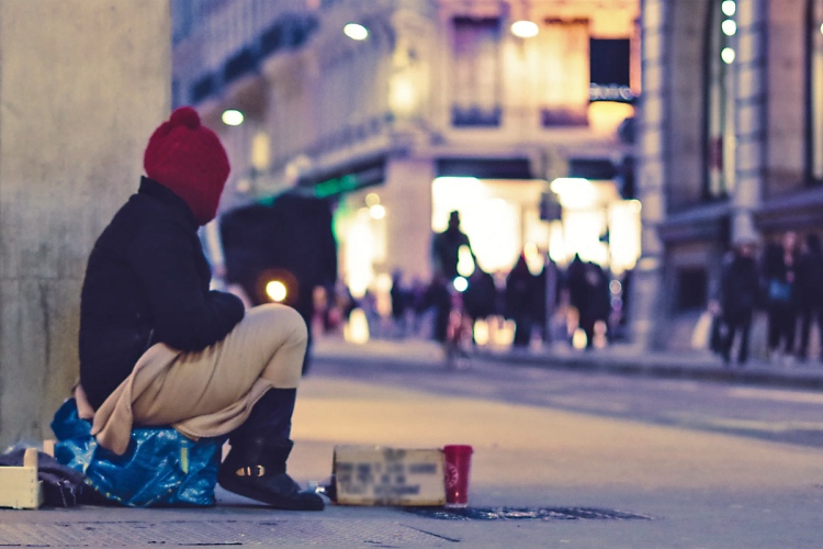 dressed in winter clothes, person sits on street as people shop at nearby lit-up storefronts.