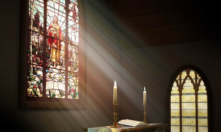 light shines through the stained glass window onto the communion table with two lit candles.